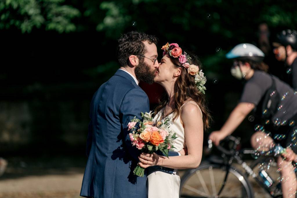 A newlywed couple kisses at the end of their wedding ceremony on an open street in the borough of Brooklyn