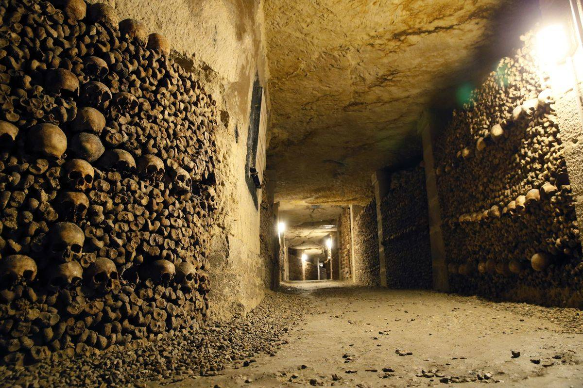 A picture shows skulls and bones stacked at the Catacombs of Paris