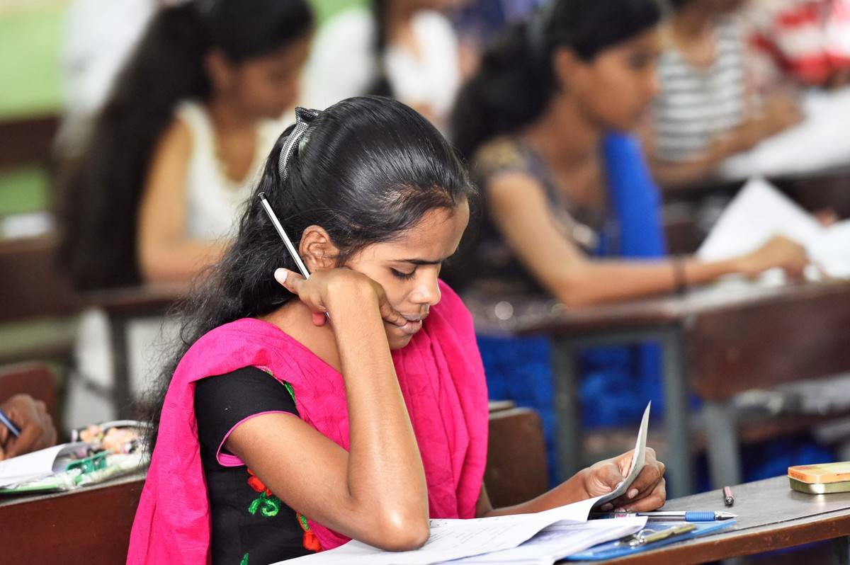 A young woman studies Gujarati in school.
