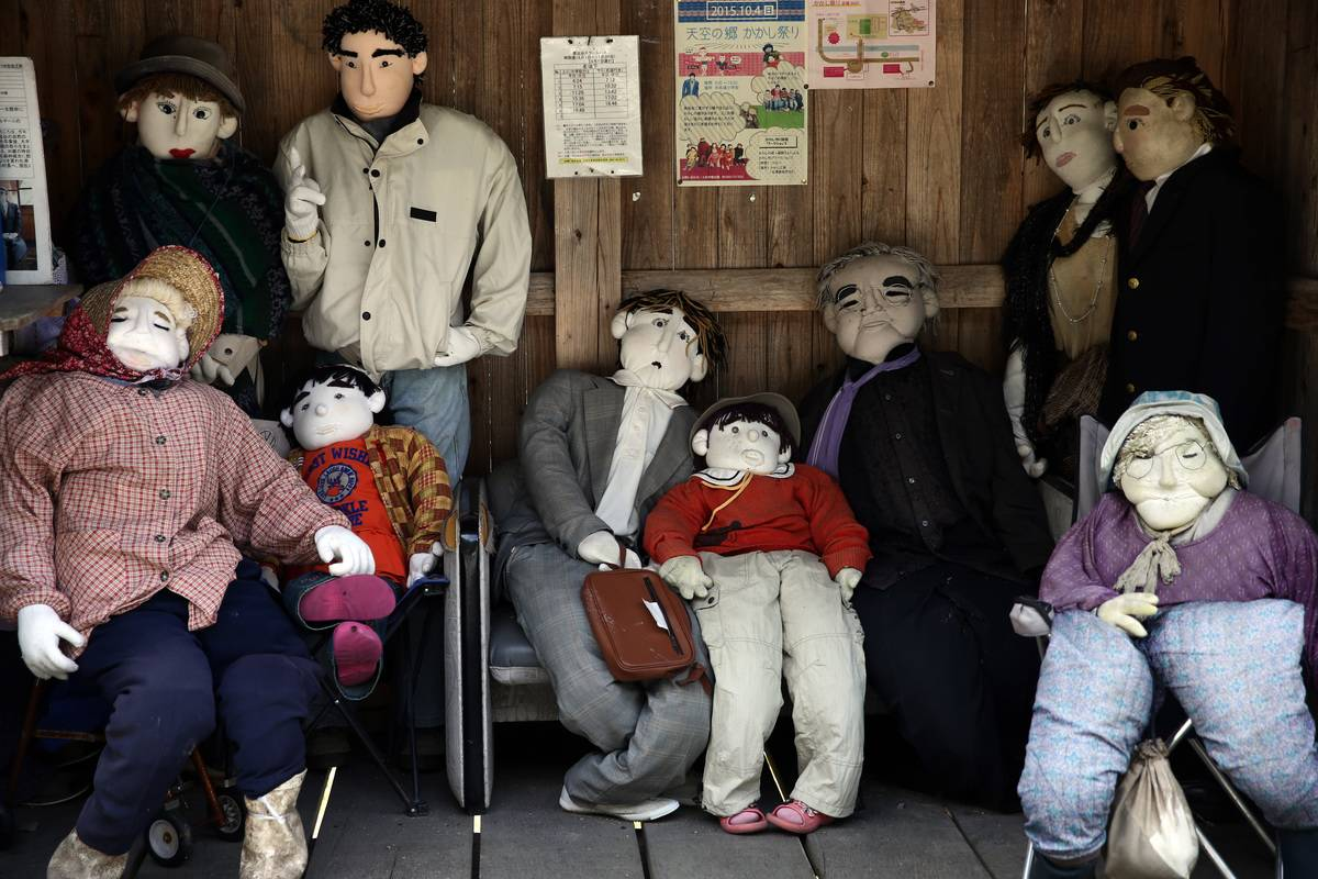 Hand-made dolls sit in a shelter