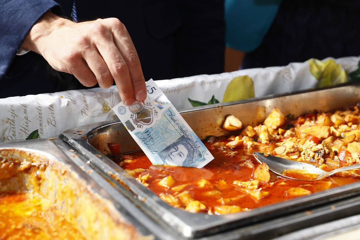 A man dips an Australian polymer banknote into a food dish because the money will not be damamged.