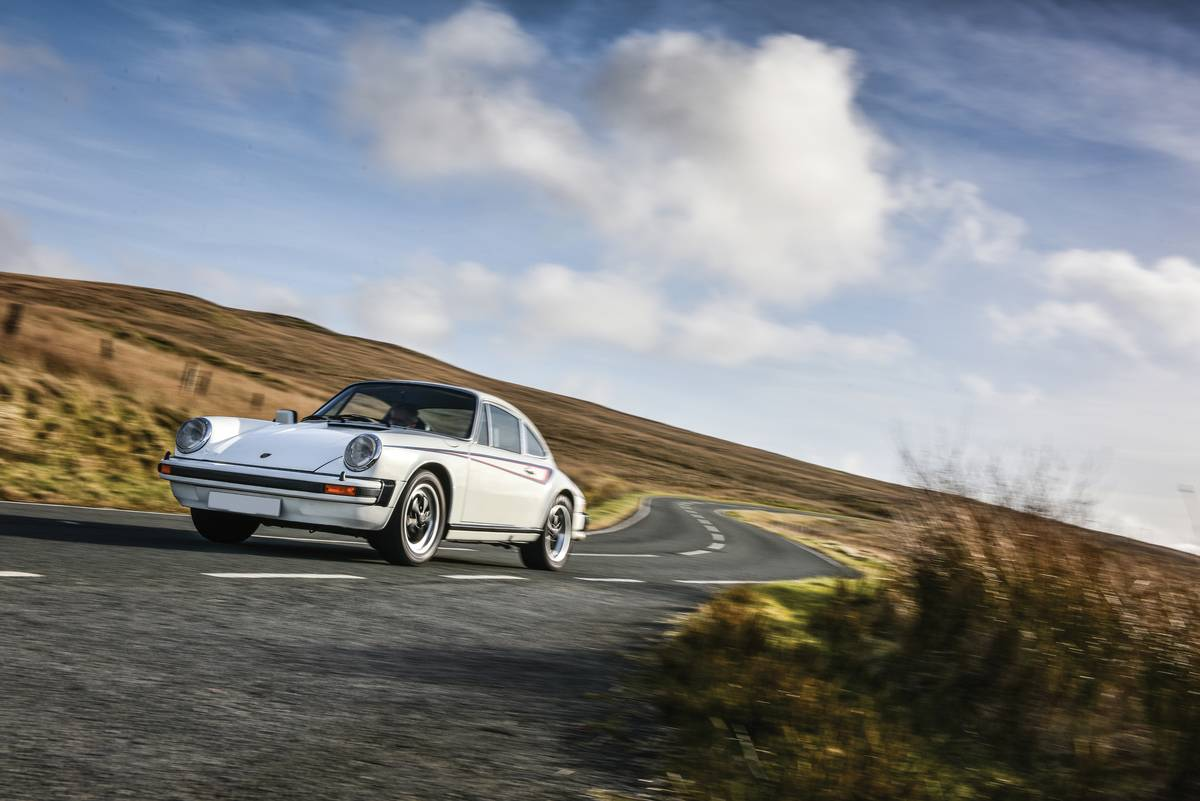 A 1978 Porsche 911 drives down a road in Wales.