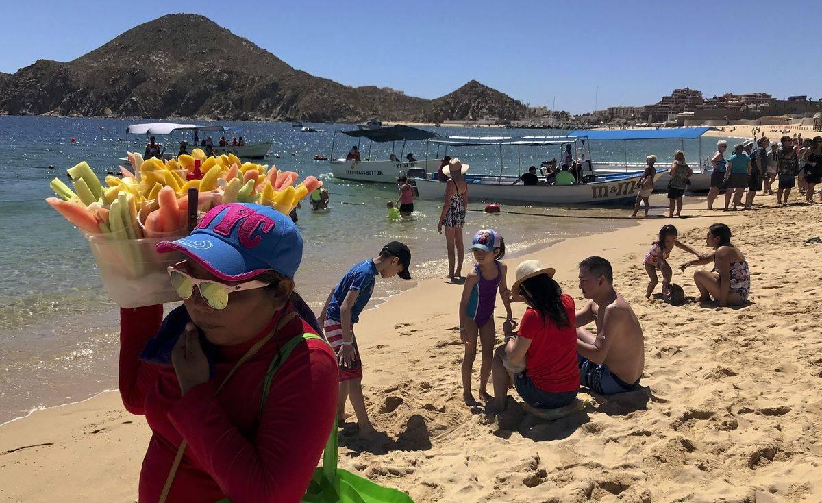 A vendor sells fruit along a beach in Mexico.