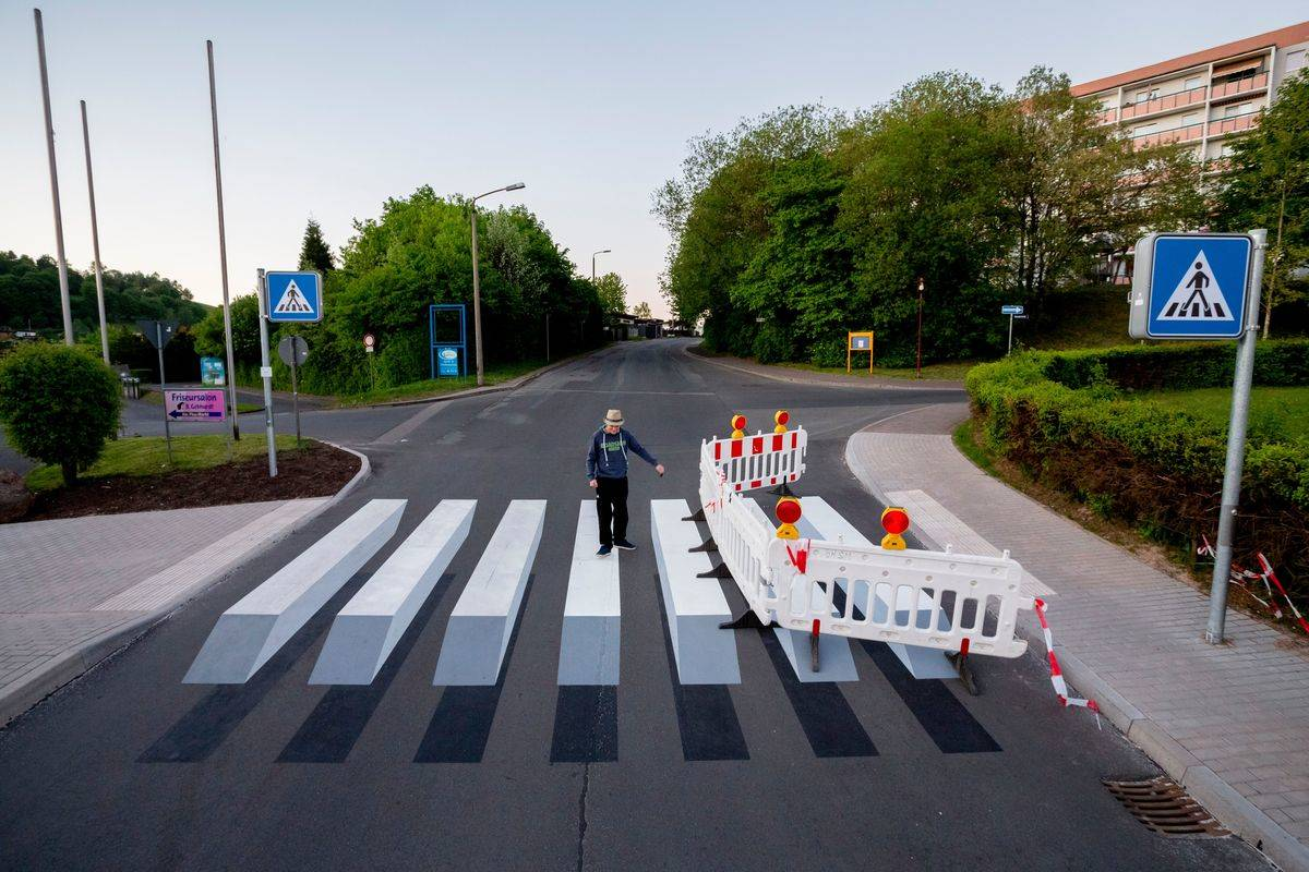 A man walks over a 3D optical illusion crosswalk.