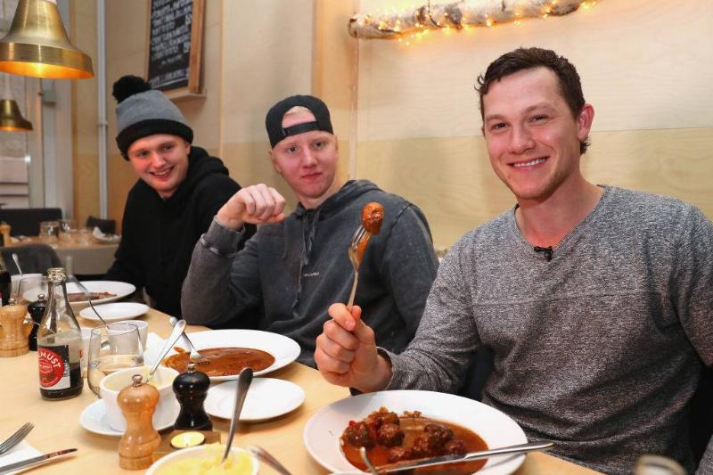 three young men eating Köttbullar