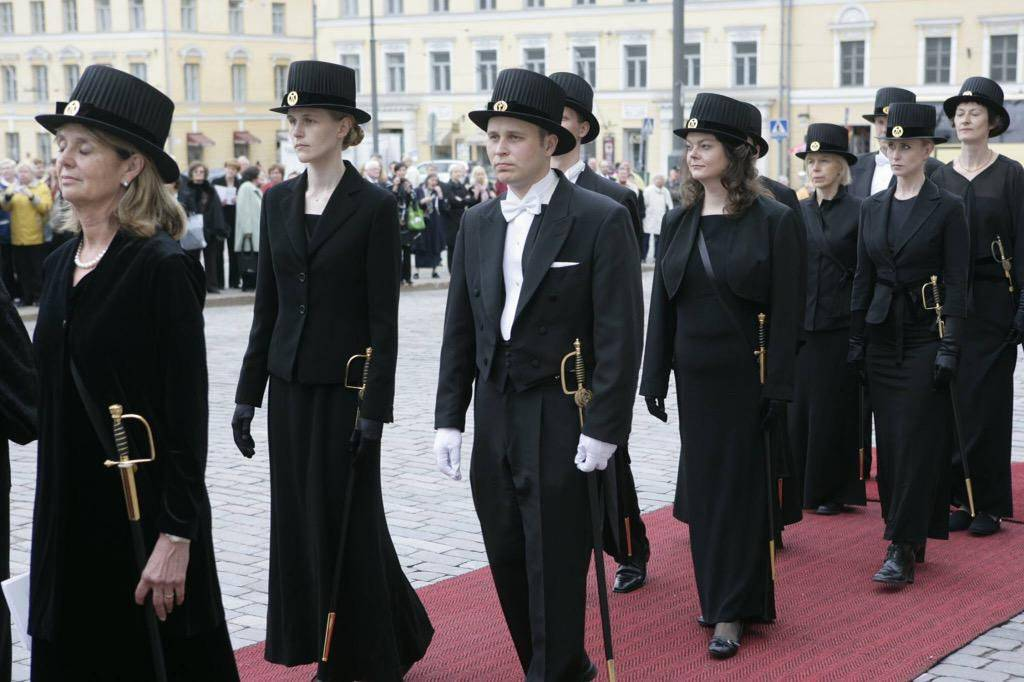 PhD Graduates stand with top hats and swords in Finland.
