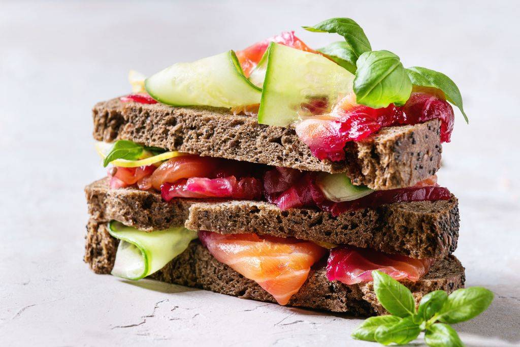 Sliced beetroot marinated salmon sandwiches with rye bread, cucumber, basil and lemon served in stack on wooden cutting board over grey blue texture background