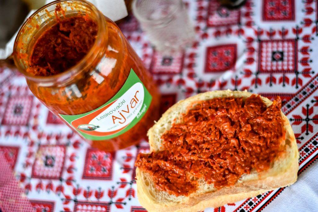 ajvar red relish in a jar and spread on a piece of bread