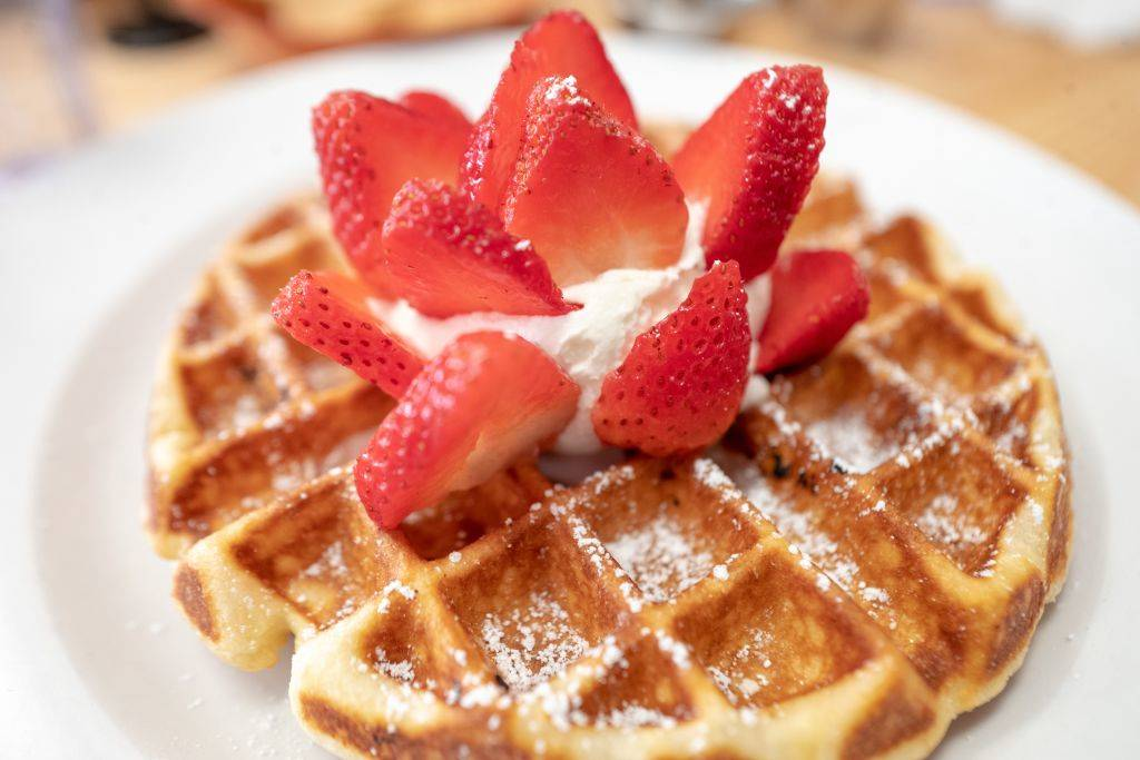 Close-up of Belgian waffle with strawberries and whipped cream on white plate