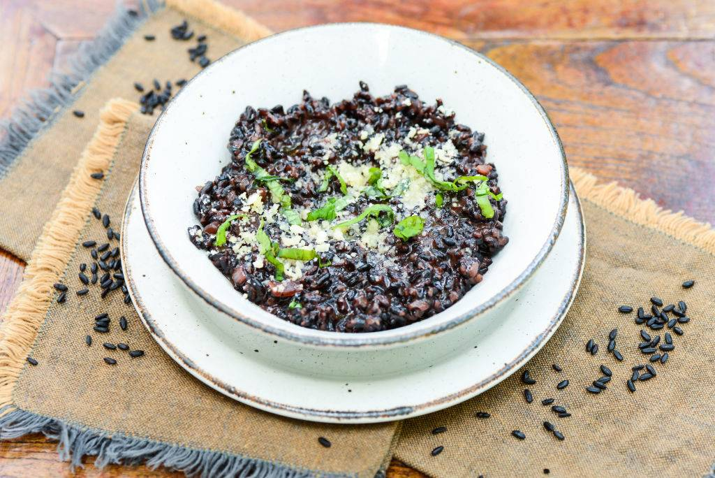 black risotto in a white bowl topped with herbs