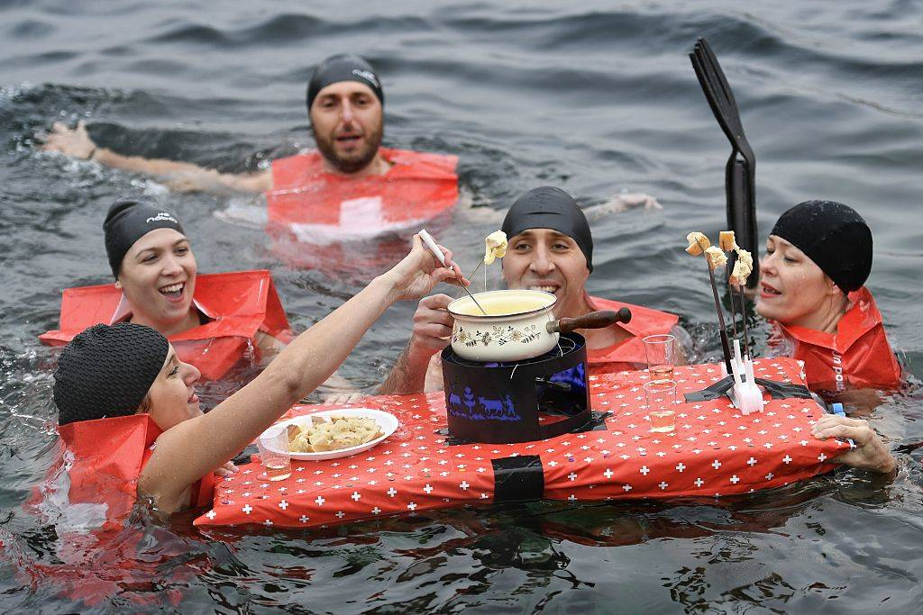 People eating a cheese fondue as they swim