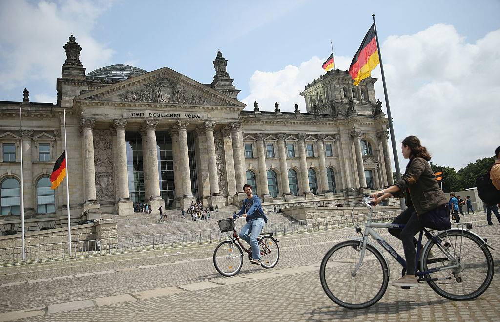 Visitors ride bicycles past the Reichstag in Germany
