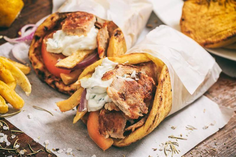 gyros sandwiches with pita bread, tomatoes, tzatziki, french fries, and onions