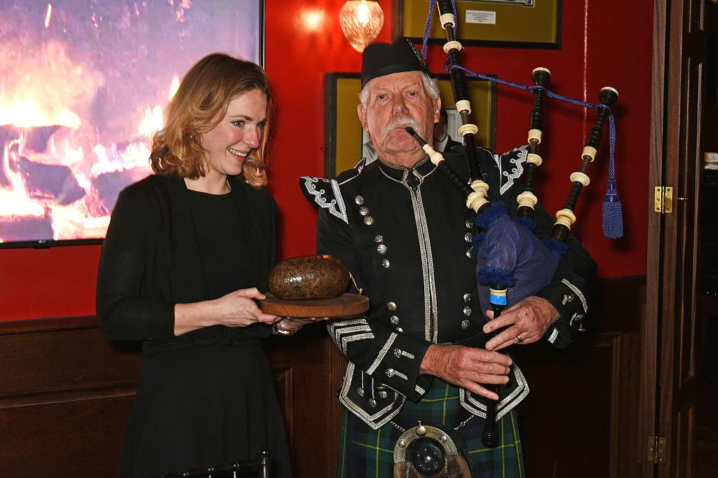 a woman holding haggis next to an old man playing a bagpipe in a kilt