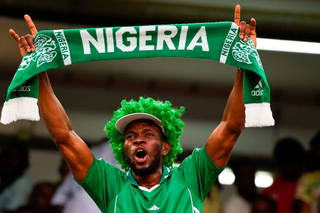 A Nigerian fan in a green wig waves a green scarf as he celebrates after the FIFA World Cup