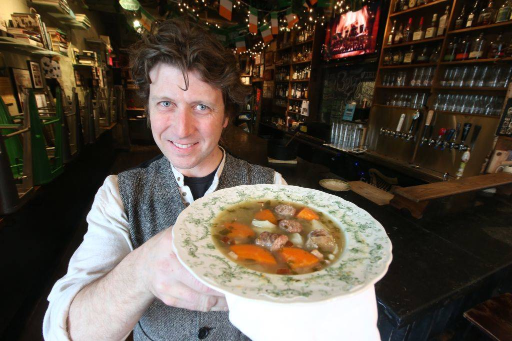 a chef holding up an irish stew of meat, carrots, and potatoes