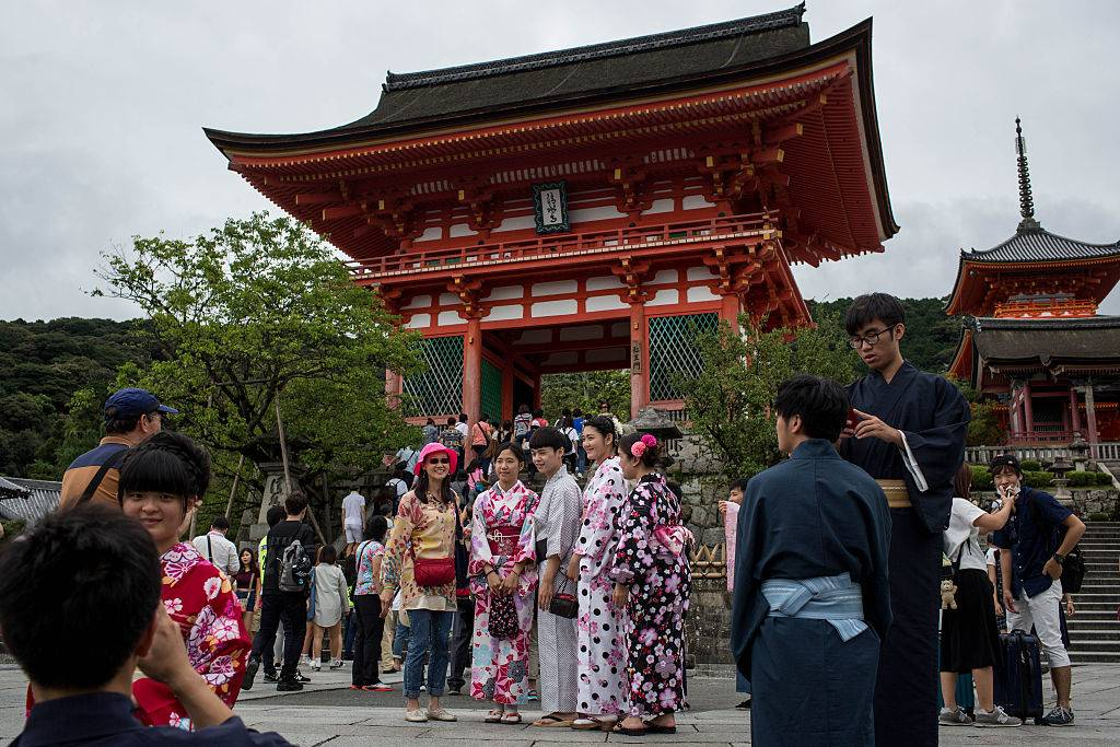 Tourists dressed in traditional Japanese outfits pose for photographs in front of the Kiyomizu Temple