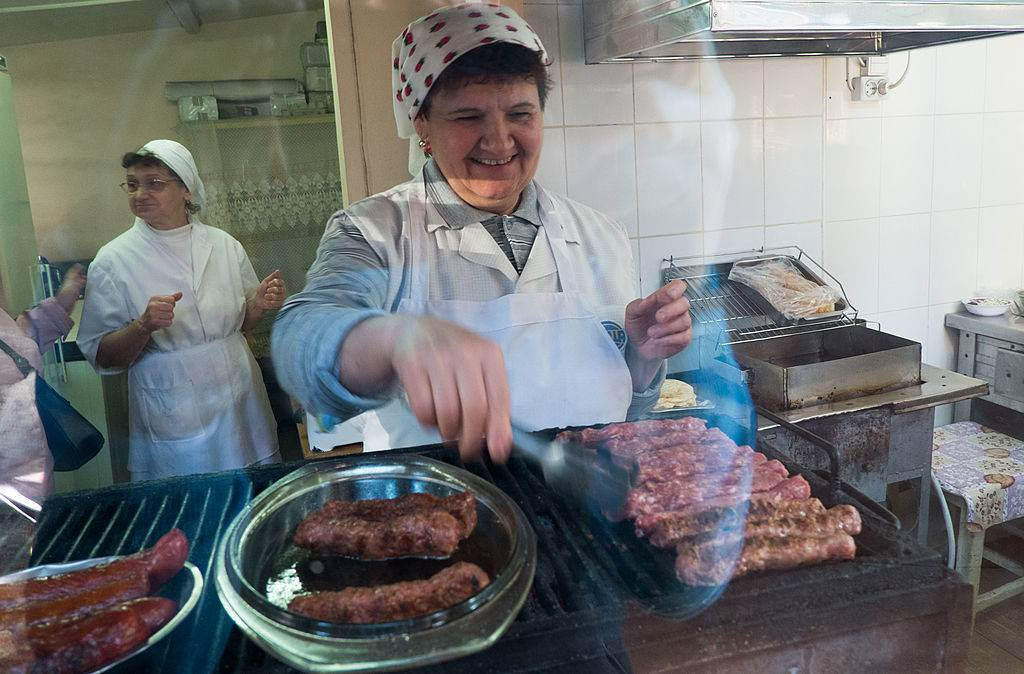 a old romanian woman cooking mititei sausages