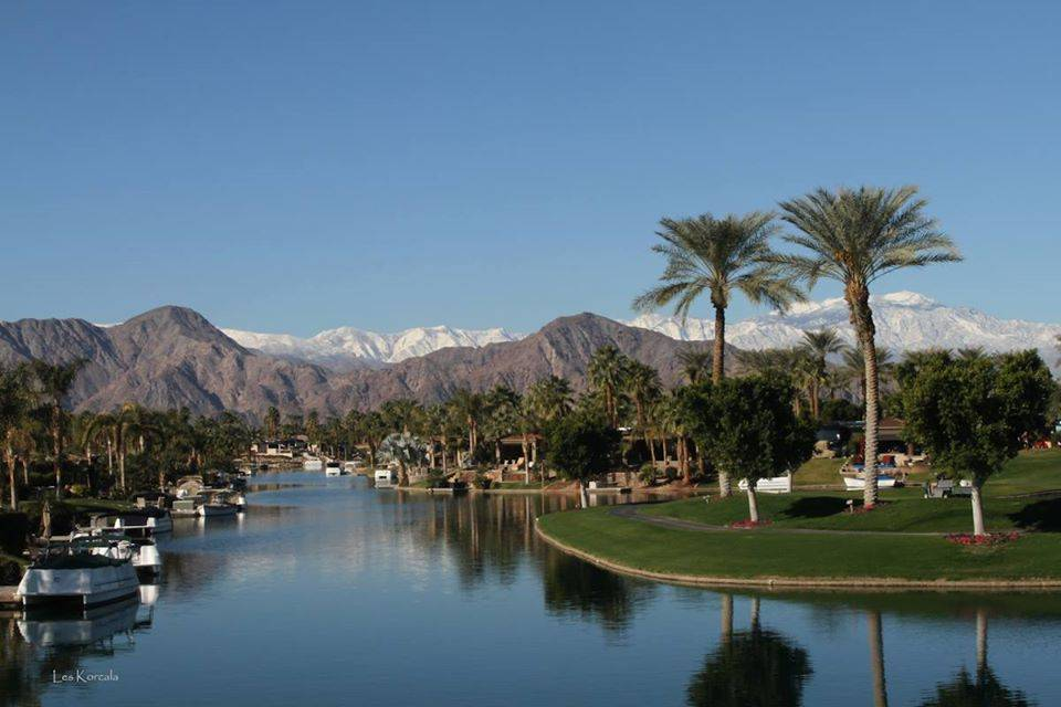 a golf course near a lake with palm trees and mountains in the background