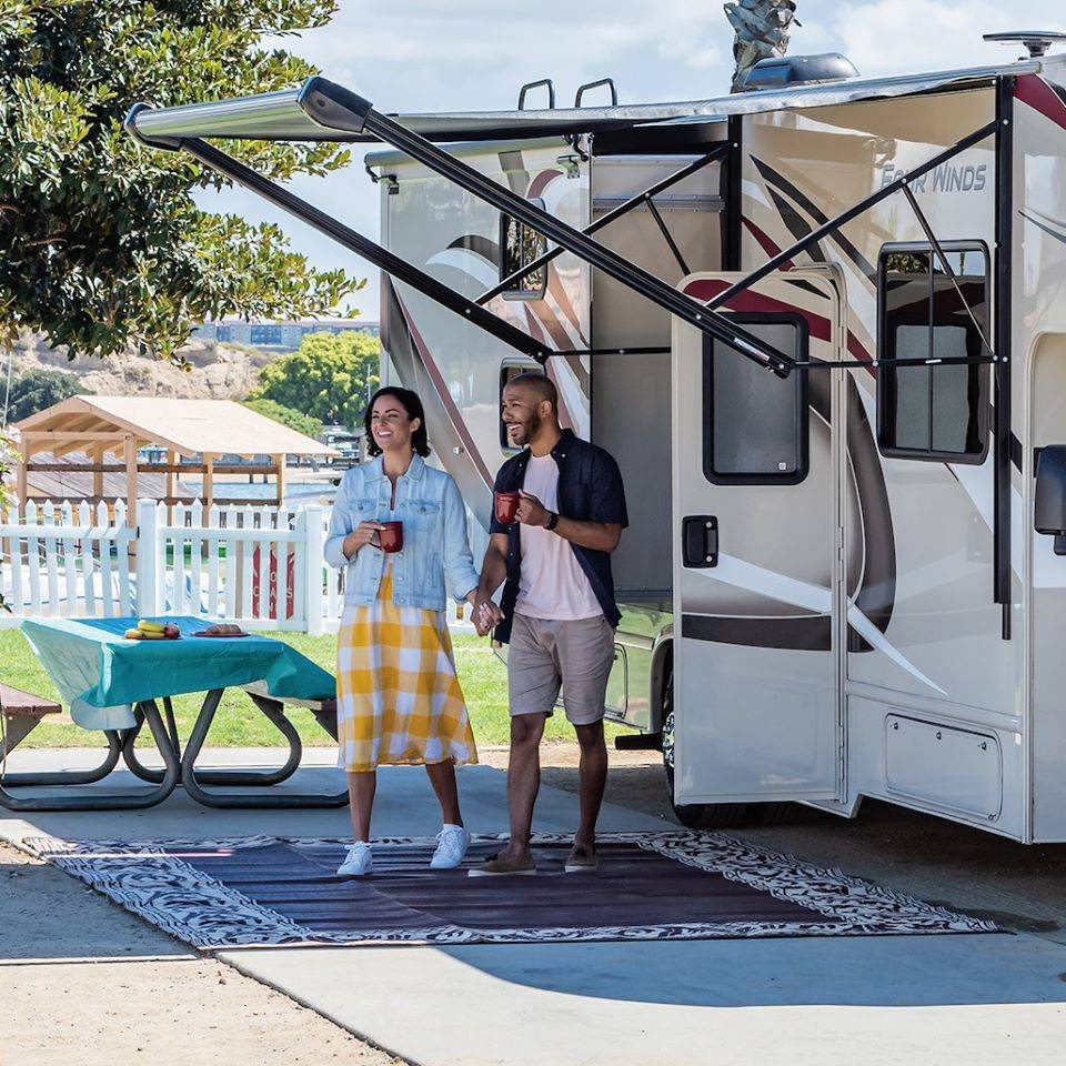 a couple standing outside an rv