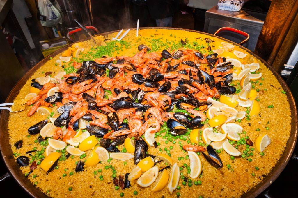 paella with rice, seafood, peas, and lemon slices