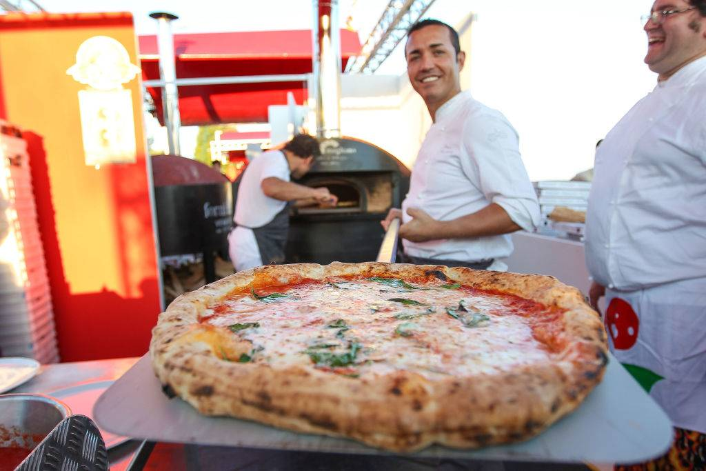 a chef taking a cheese pizza out of an oven
