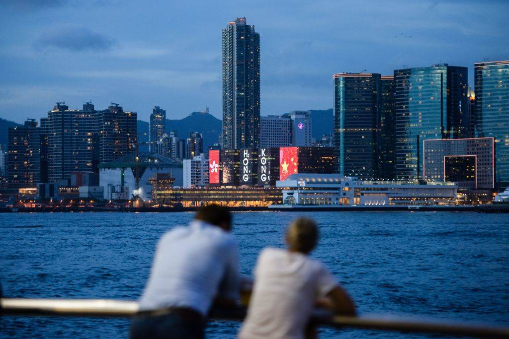Two friends chat in front of a view of Victoria Harbour and a light display in Hong Kong