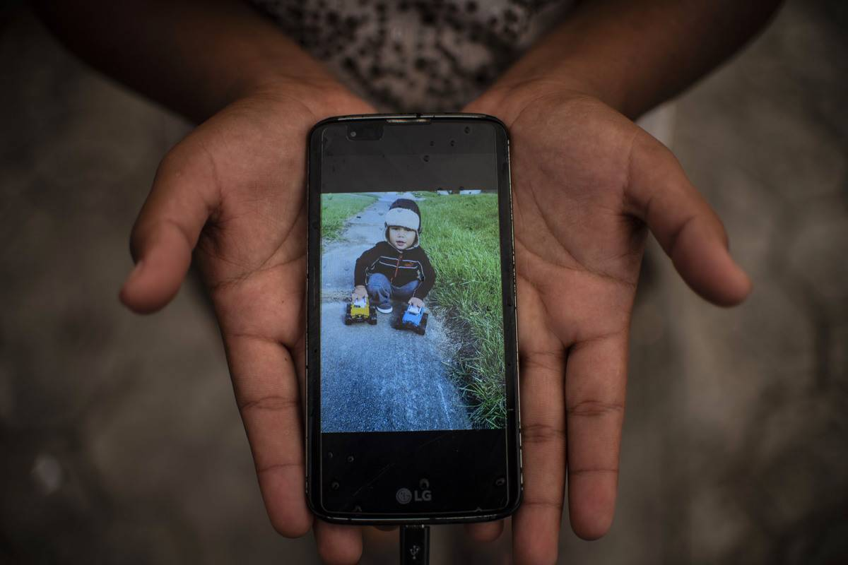 Honduran woman shows a picture of her son on her mobile phone
