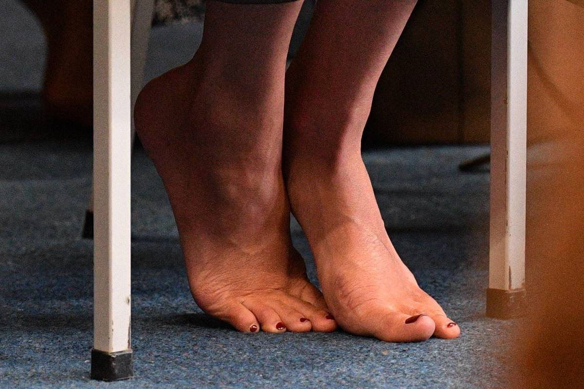 person's bare feet under table
