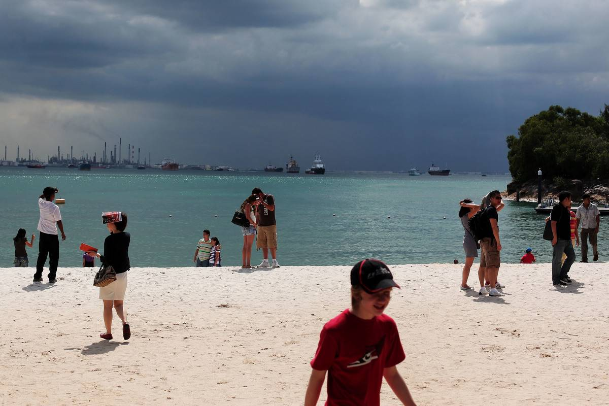 Tourists stand on the beach at Sentosa Island with oil rigs in background