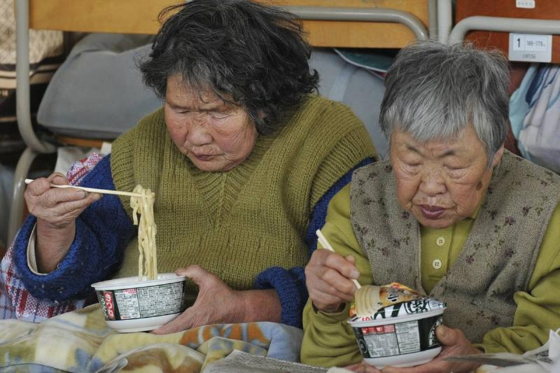 two women eat instant noodles for lunch