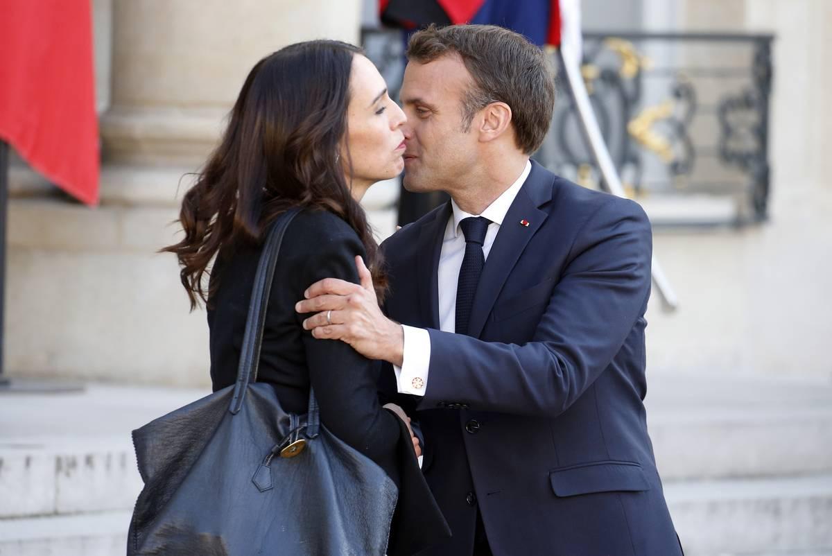French President Emmanuel Macron kisses New Zealand Prime Minister Jacinda Ardern on the cheek