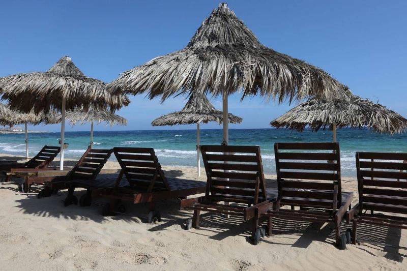 Empty sunbeds lie along a beach in the Cypriot resort town of Ayia Napa