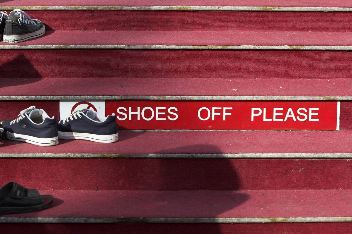 Shoes and Remove Shoes sign on carpet steps Wat Chalong Phuket Thailand
