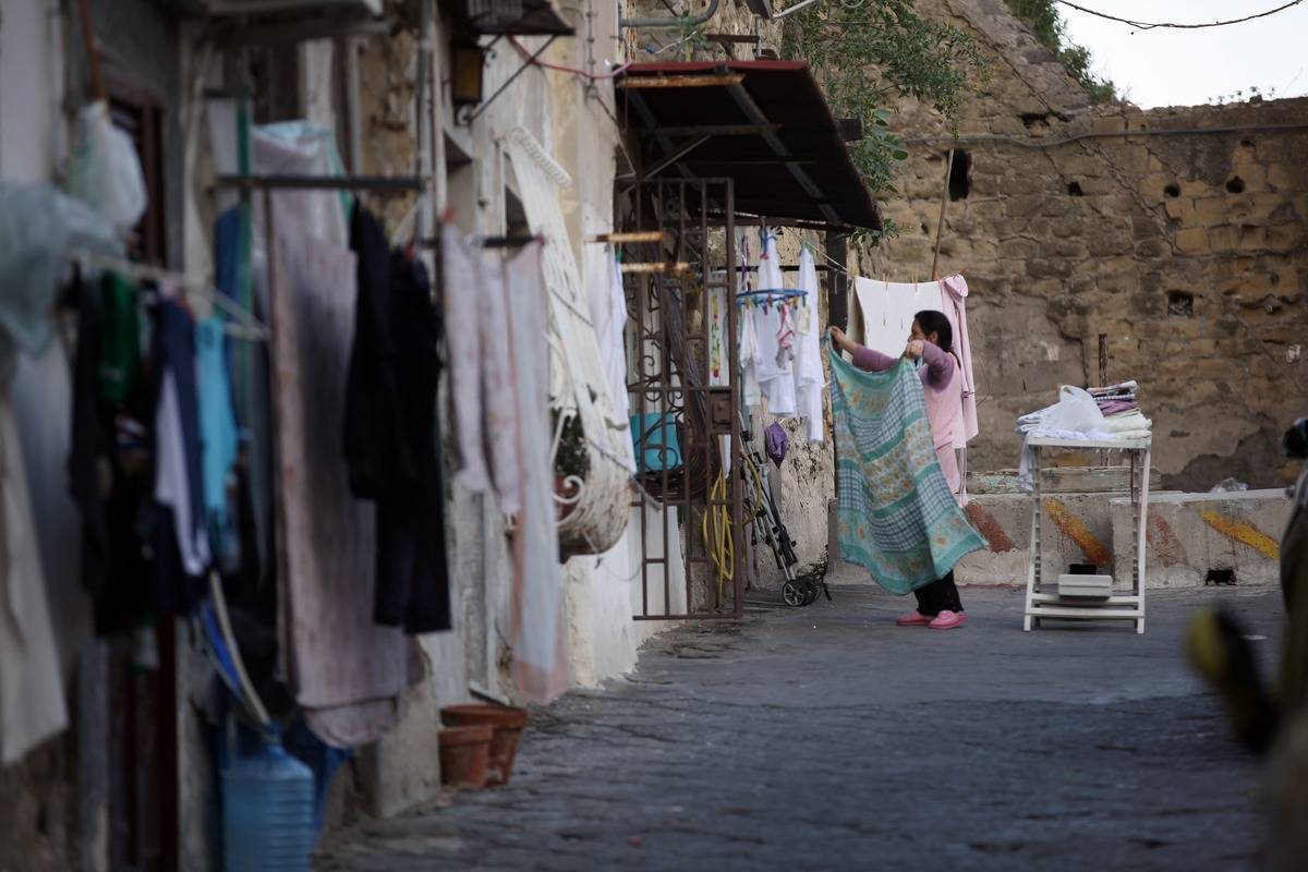 A woman hangs washing out to dry, a familiar site in the poorer areas of Naples