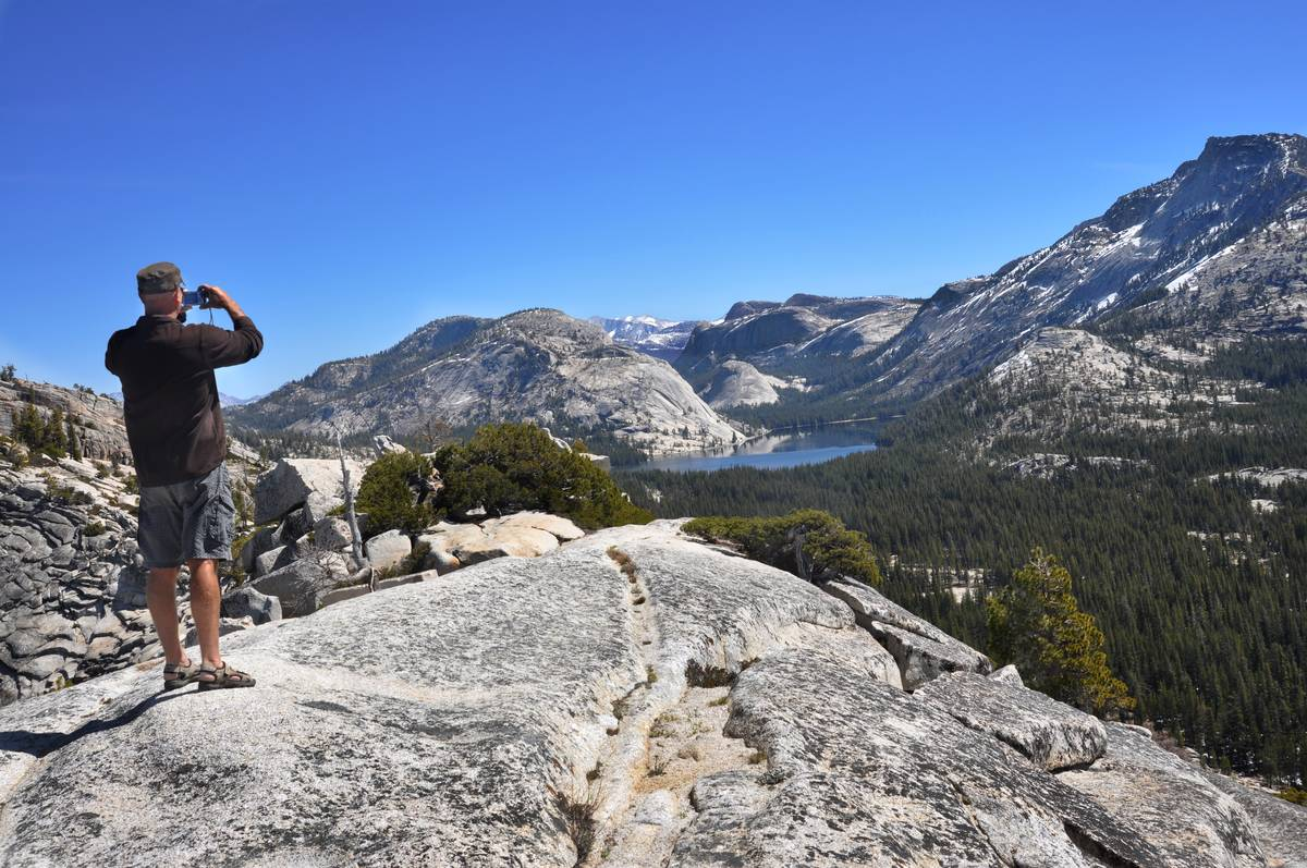 A visitor to Yosemite National Park in California admires the view of Tenaya Lake from Olmsted Point, a popular destination in the park featuring views of Yosemite Valley