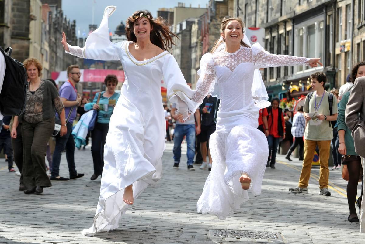 women running down streets of edinburgh dressed as brides