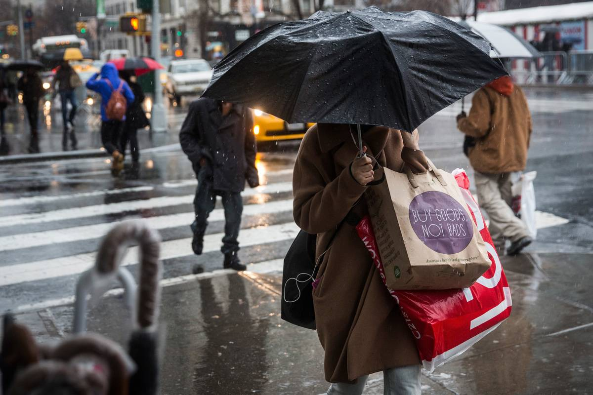 People walk along the sidewalk in the rain holding shopping bags