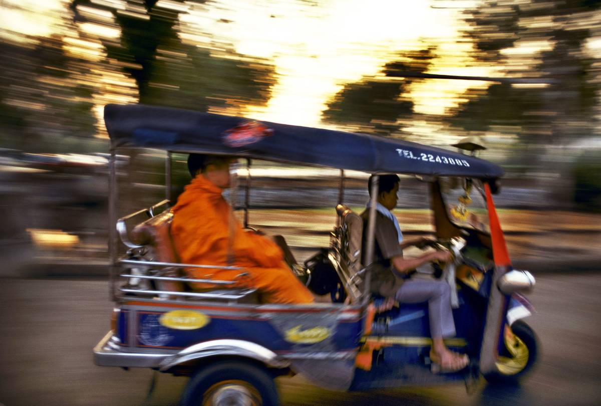 Buddhist monk in the back of a three wheel tuk tuk taxi on a road in Bangkok