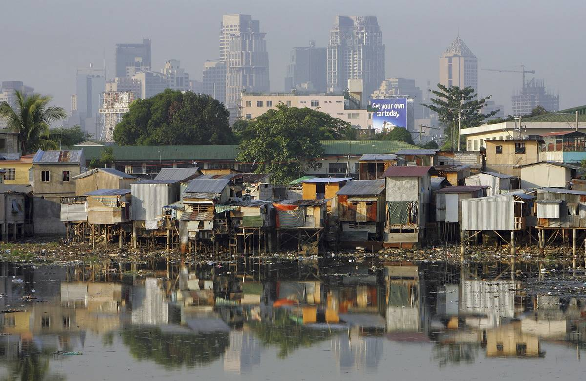 Shacks stacked on top of each other stand out from the financial district of the skyline along the polluted Maricaban River in the slums in Manila, Philippines