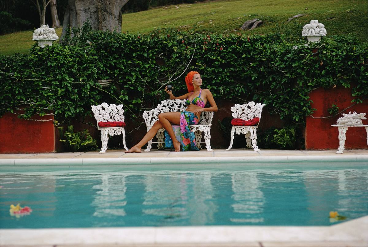 woman relaxes with a drink by a swimming pool in Bermuda