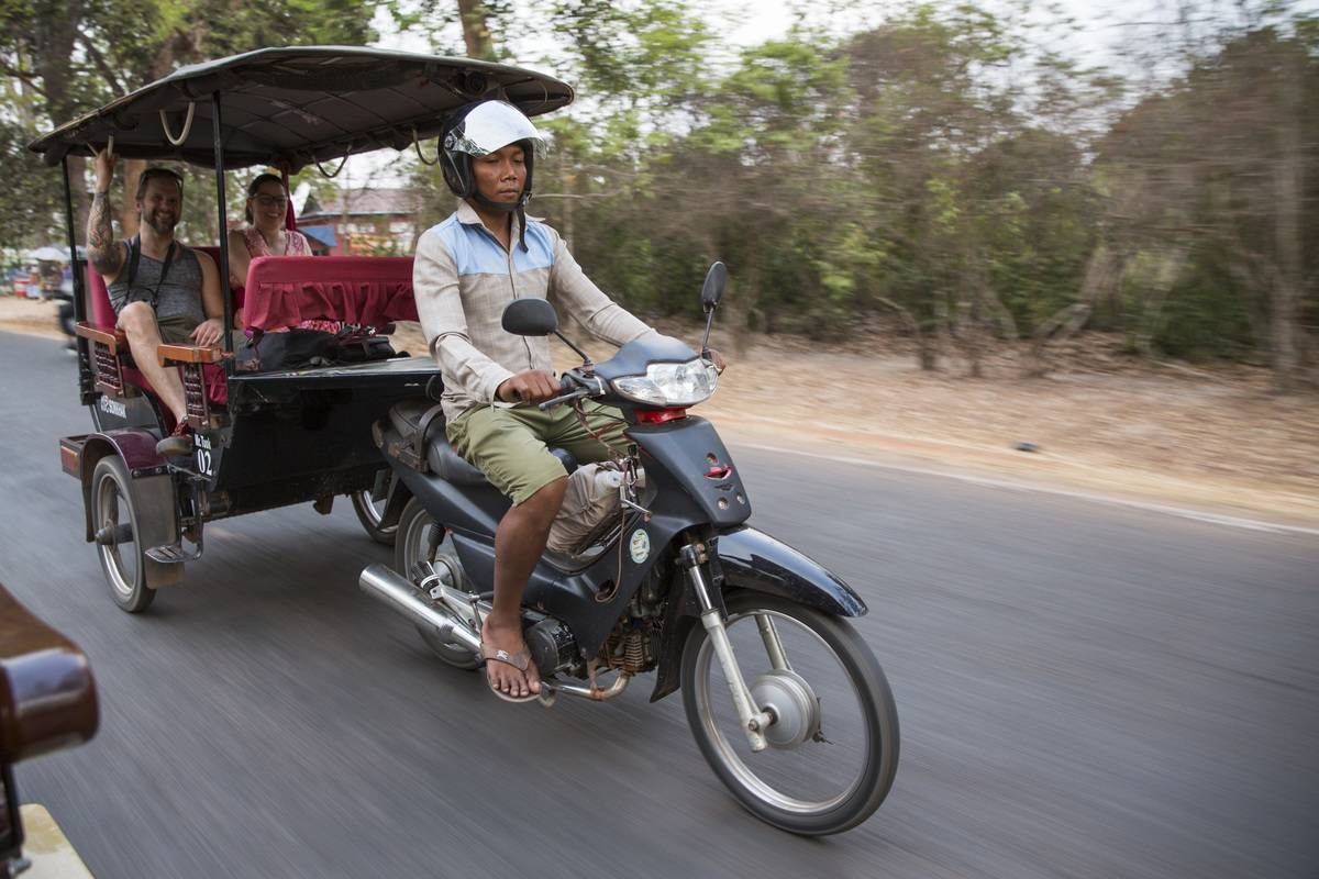 A Cambodian man drives two smiling Western tourists on his a motorbike Tuk Tuk