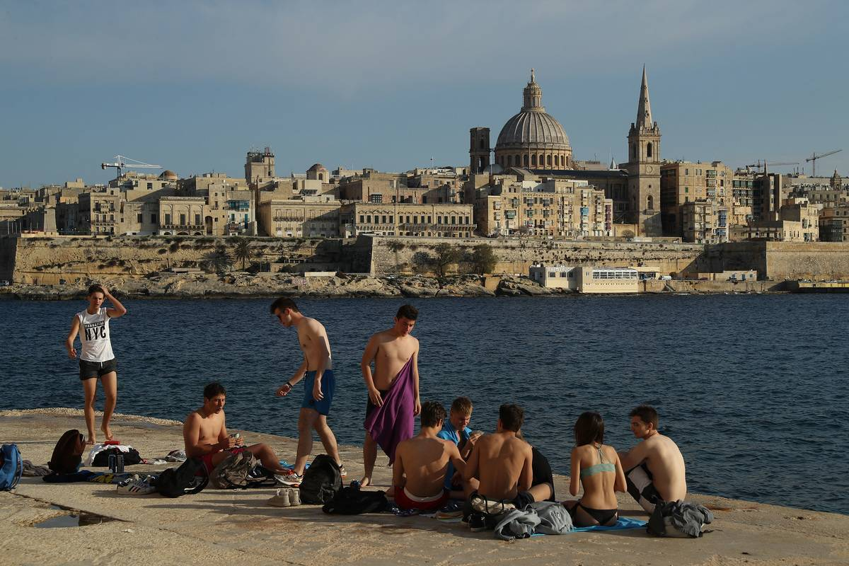 young people relax on the waterfront as Valletta, including the dome of the Basilica of Our Lady of Mount Carmel,