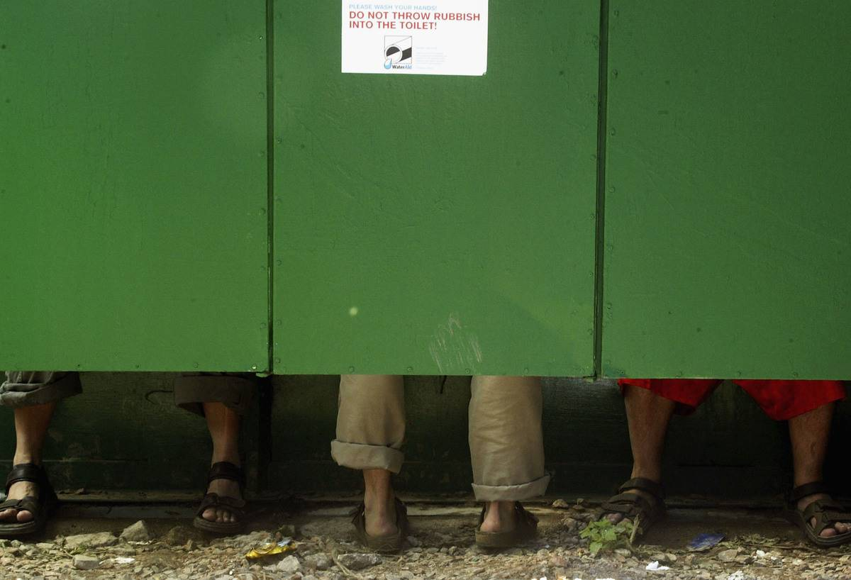 Festival-goers use neighboring toilet cubicle stalls
