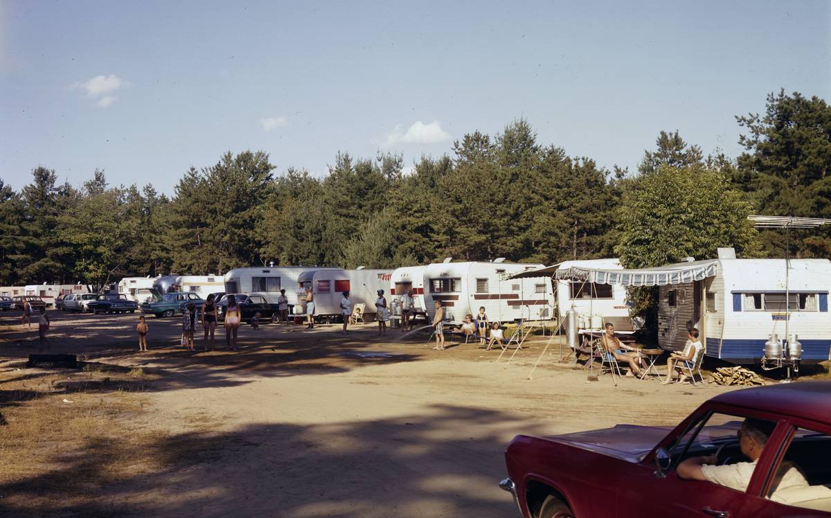 People relax and talk amid a row of parked campers and trailers at the Wagon Wheel Trailer Park