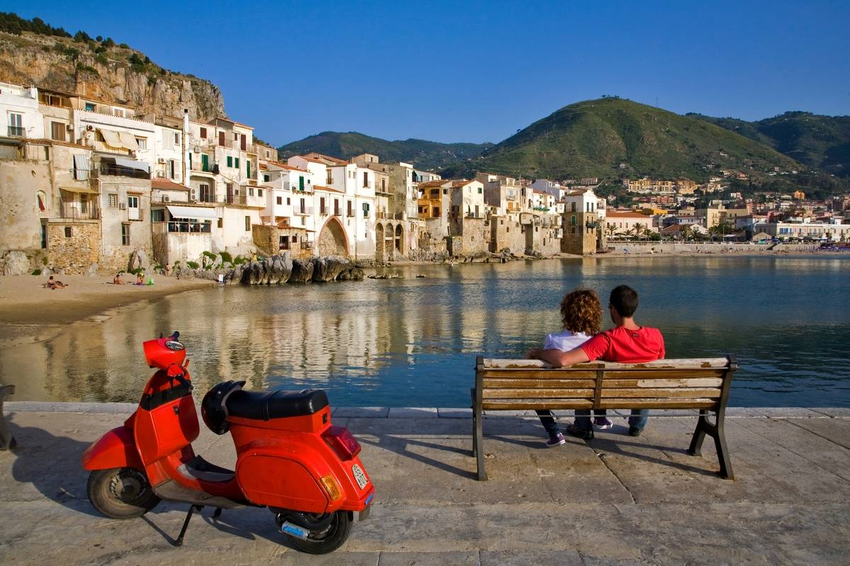 couple sitting on waterfront in sicily