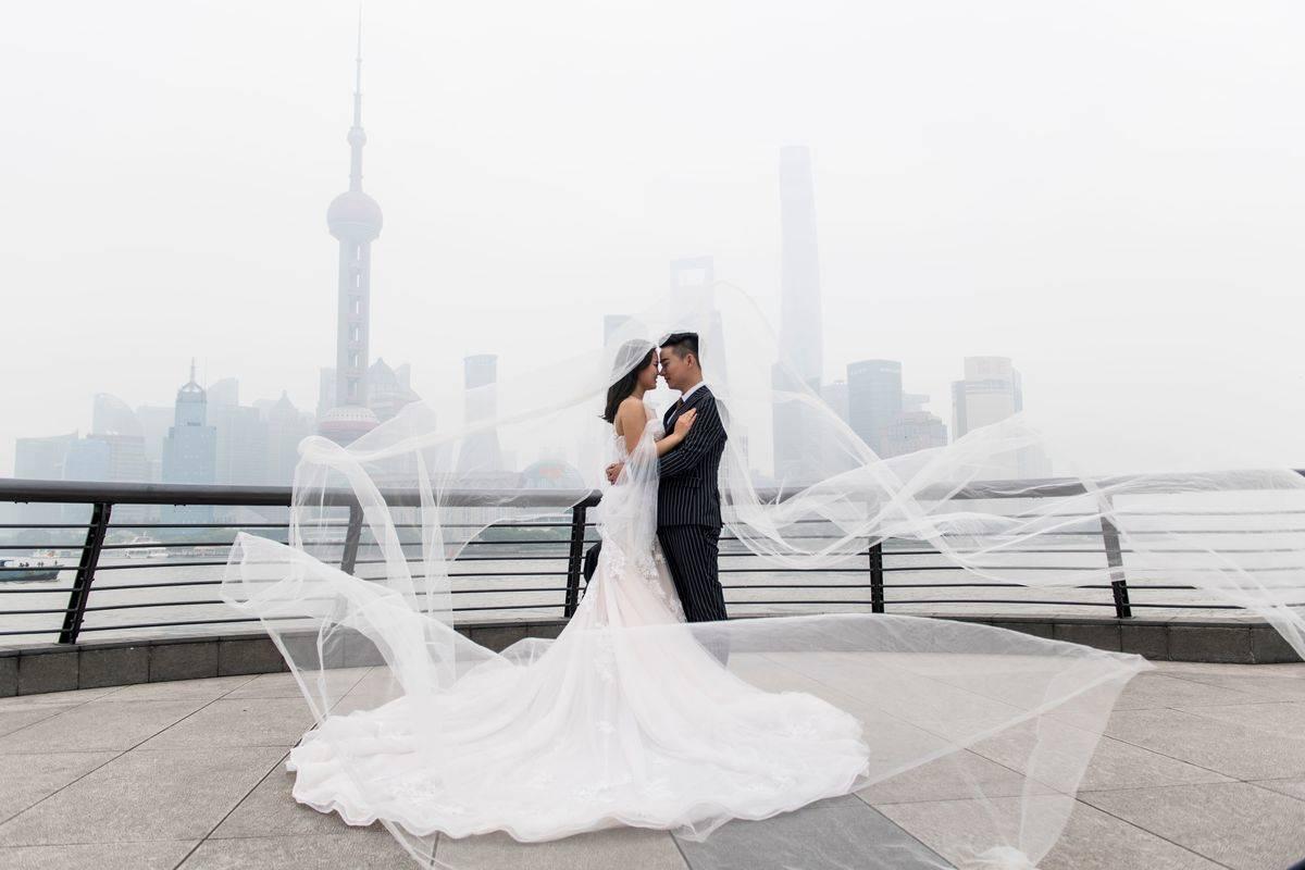 A couple poses for a wedding photographer