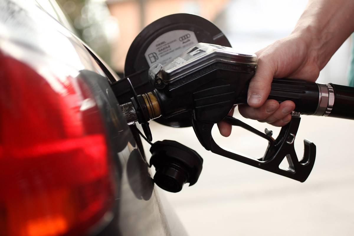 A gasoline station attendant pumps diesel into a car