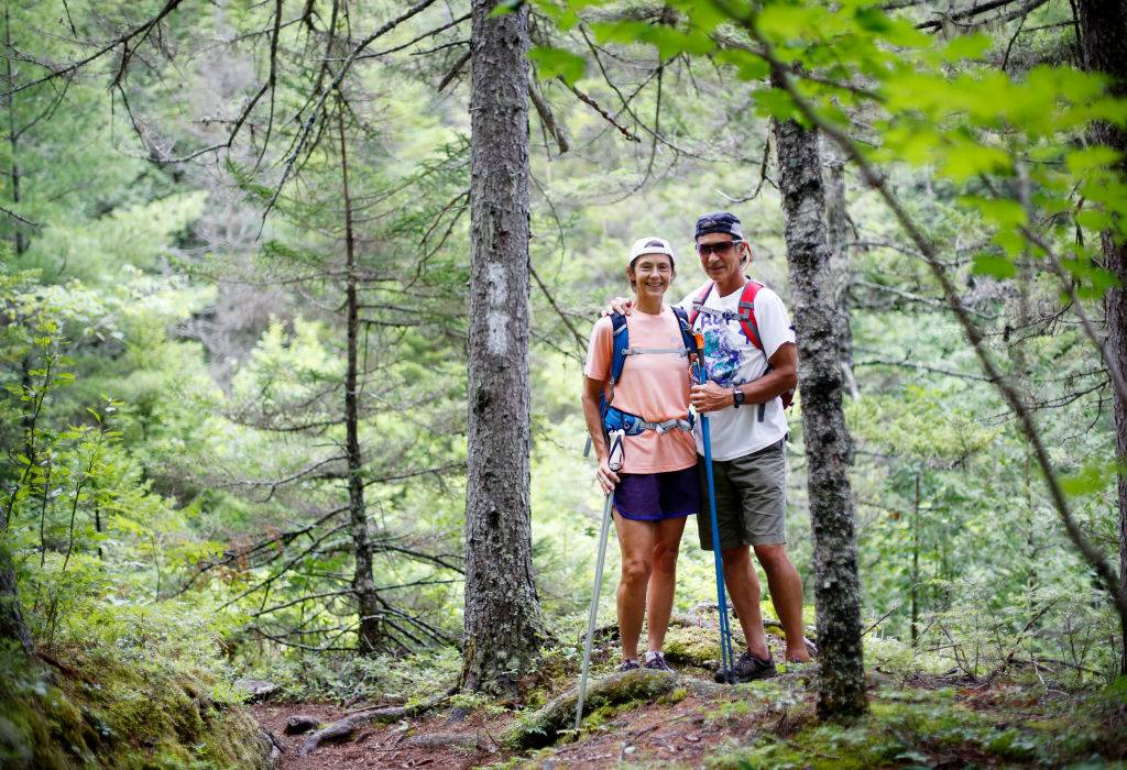 a man and woman backpacking through the appalachian trail in maine