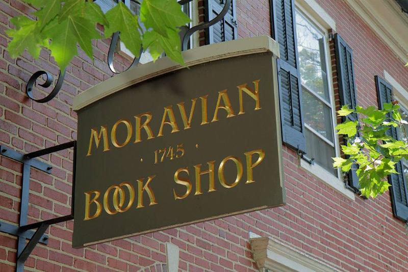 a sign for the moravian book shop outside a red brick building